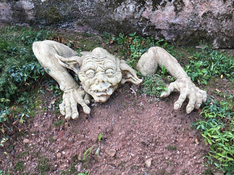Gargoyle, eine den alten Wasserspeiern nachempfundenen Figuren scheint aus dem Gartenbeet zu krabbeln