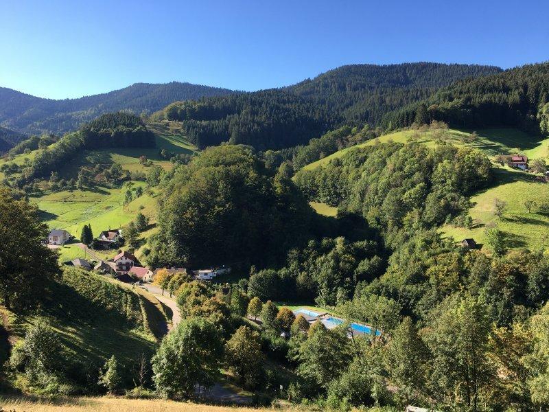 Grüne Wiesen, dunkel bewaldete Kuppen, blauer Himmel, im Vordergrund ein Schwimmbad, so fängt die Tour auf dem Himmelssteig an