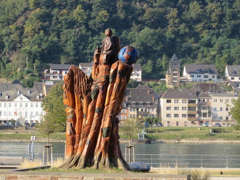 Eine bunte Holzskuptur am Fluss, am gegenüberliegenden Ufer sieht man die Häuser einer Ortschaft