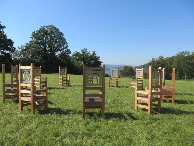 Eine grüne Wiese, darauf zwölf große Holzstühle. In die Lehne der Stühle sind große Symbole eingearbietet. Am hinteren Rand der Wiese stehen Bäume. Über dem allen wölbt sich ein blauer Sommerhimmel.