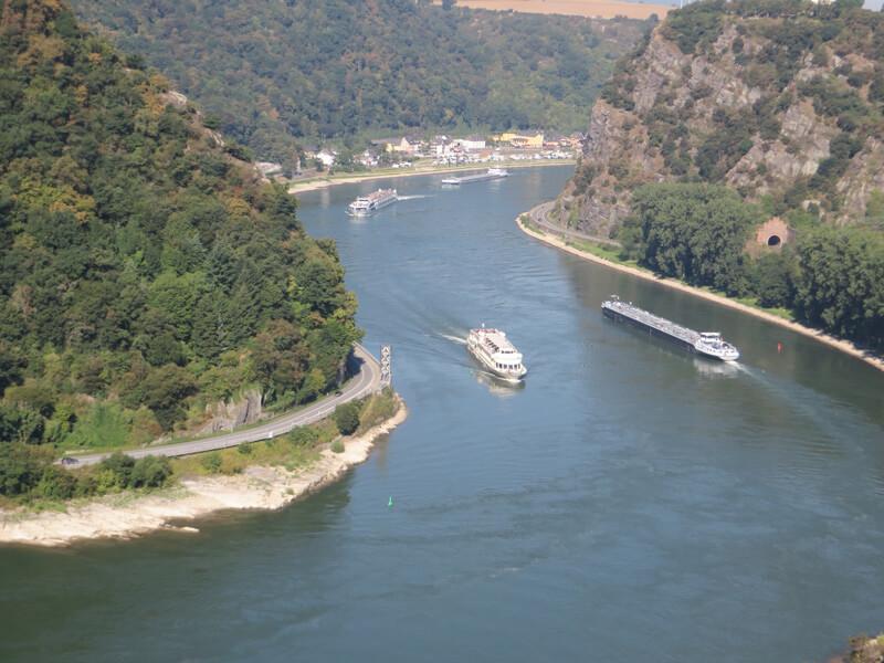 Blick von oben auf den großen Fluss, den Rhein, links und rechts schroffe Hänge, der rechte ist der berühmte Loreleyfelsen. In dieser engen Flussschleife sind früher viele Schiffe verunglückt.