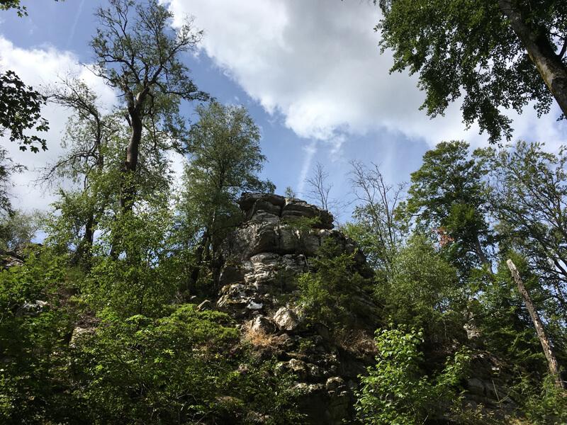 Grüne Laubbäume, zwischendrin ein zerklüfteter Felskopf, das alles unter blauem Himmel mit weißen Wolken