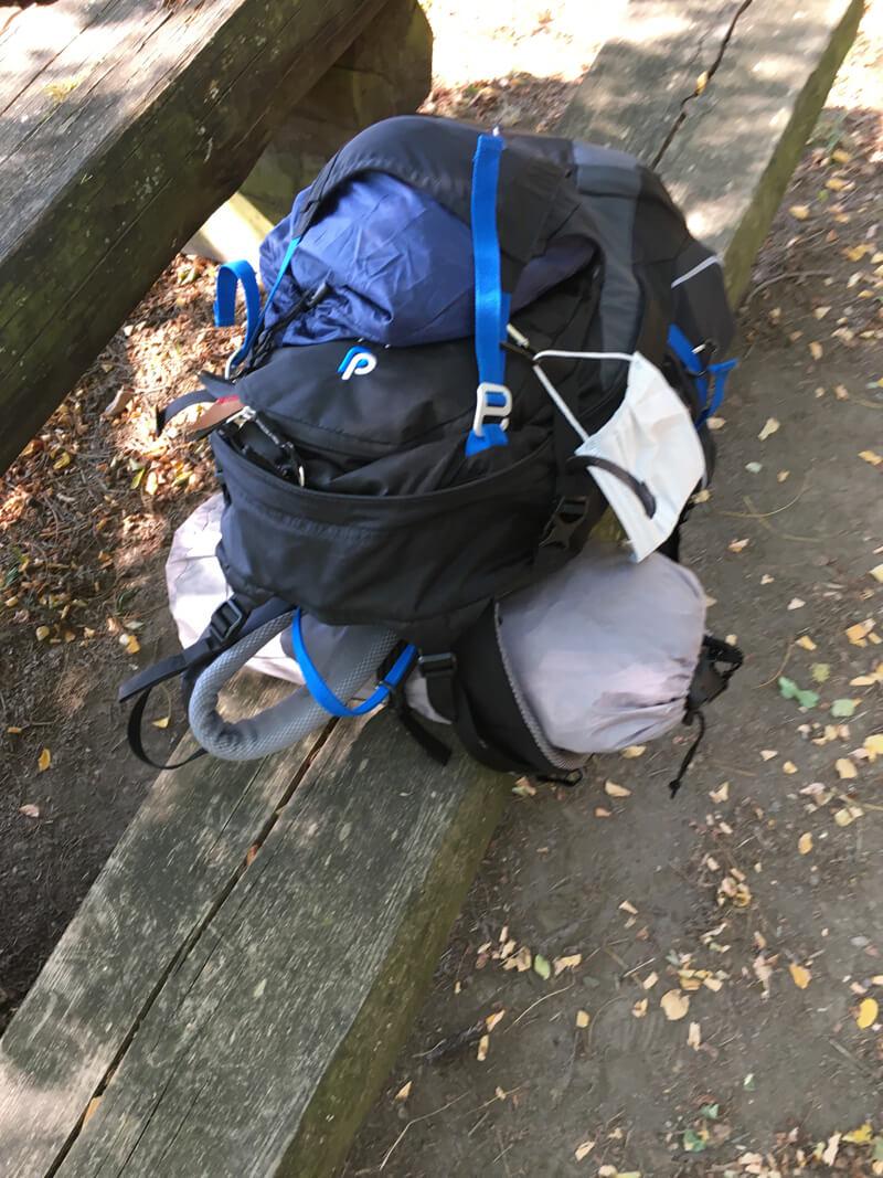 Ein Rucksack, ein Zelt, auf einer alten Holzbank