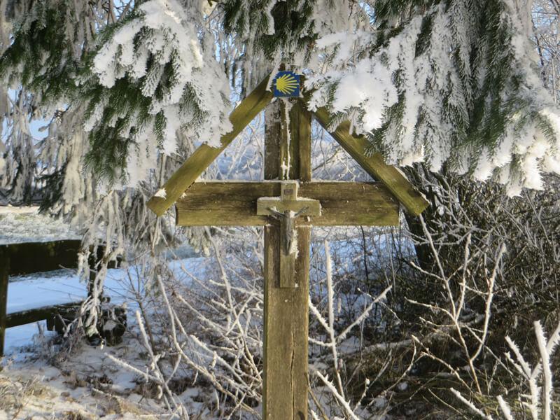 In schlichtes Holzkreuz trägt das Symbol des Jakobspilgerweges, darüber schneebeladene Zweige einer Fichte
