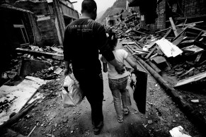 A young girl and her father have returned to the ruins of their home to see if there's anything left to save. The mother seen in the wedding portrait is in hospital, wounded but alive.