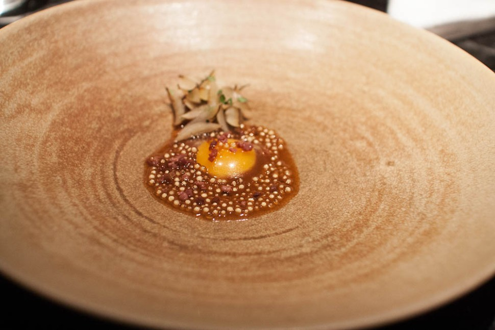 """Charred onions and quail egg gently cooked in roasted bone marrow, with aged """"fenalår"""" and onion vinaigrette."""