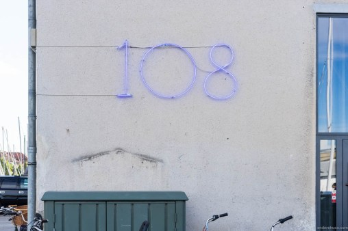 108 in neon lights on the wall