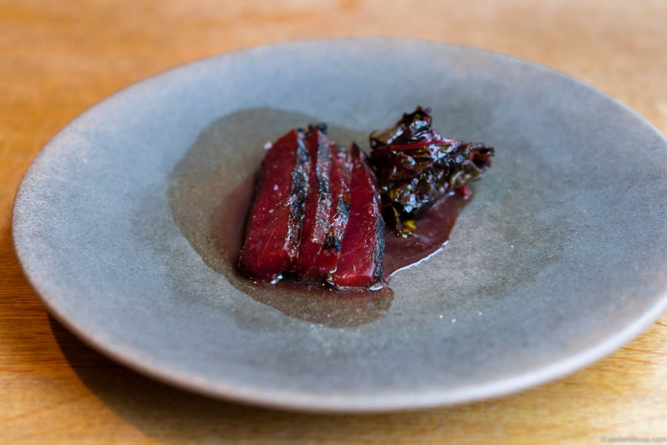 """Red beet """"beef"""" and red wine sauce infused with """"søl"""" (Icelandic seaweed). Served with a fried beet leaf on the side."""