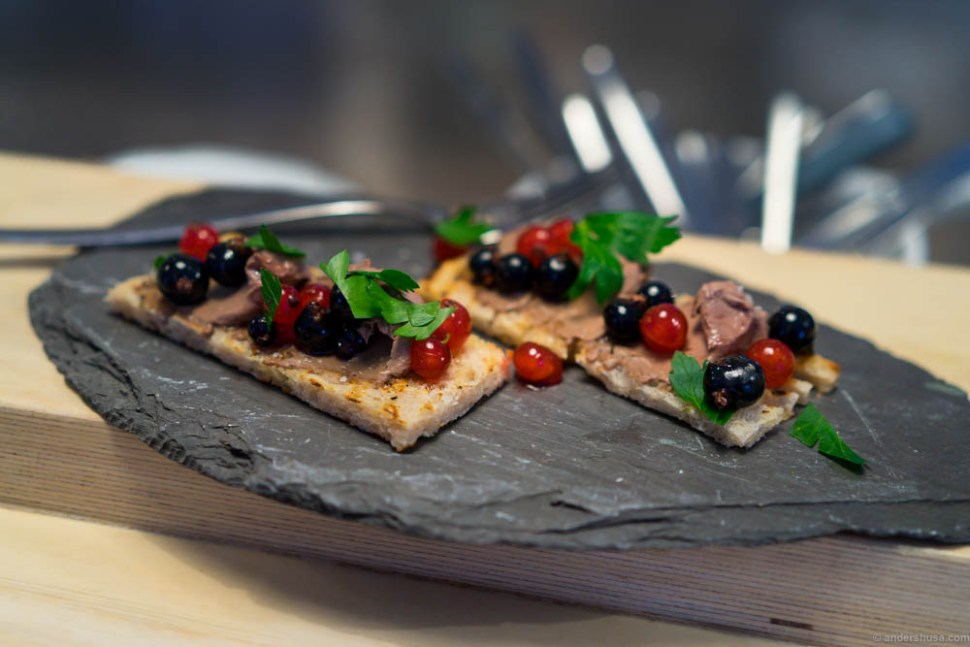 Chicken liver on bread with red and black currants.