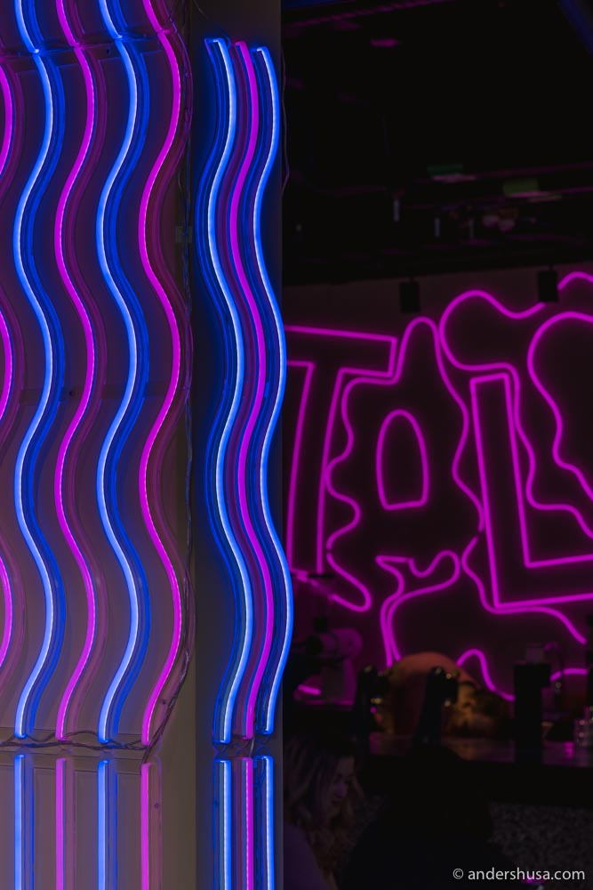 Neon signs and bright lights illuminate the fun space.