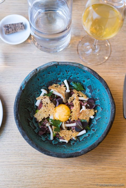 Beef tartare with pickled mushrooms and an egg yolk.