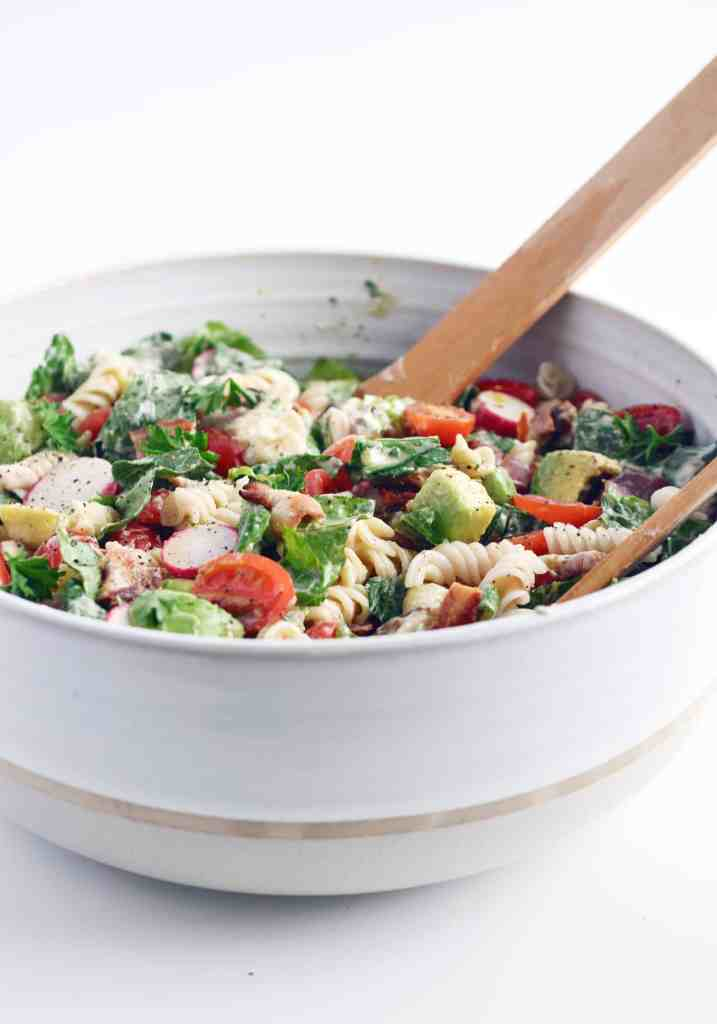 mixing BLT pasta salad with wooden spoons