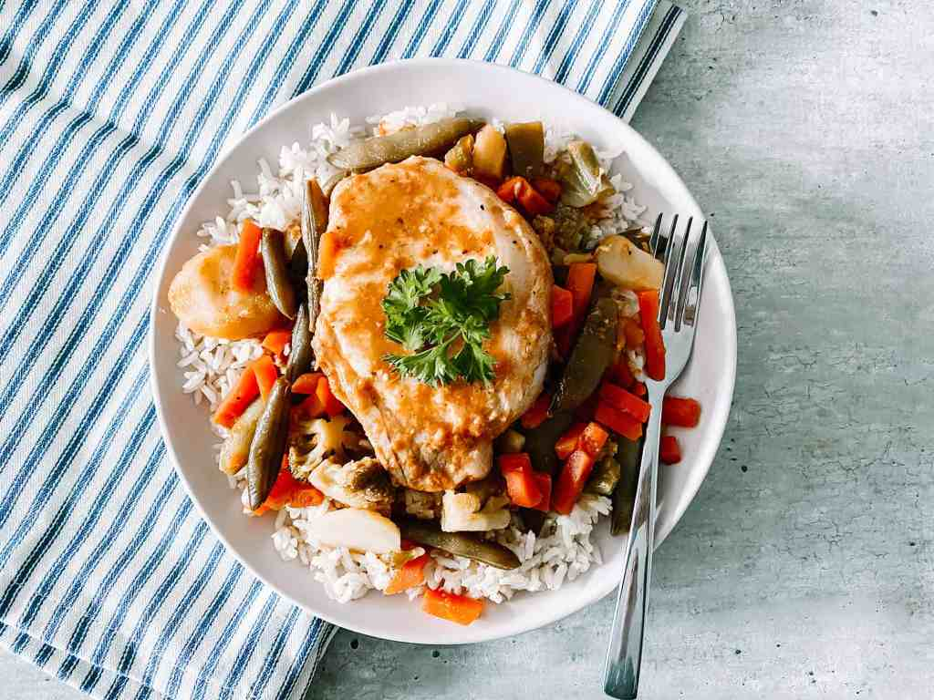 crockpot freezer meal sweet and tangy pork chops served on a plate with rice