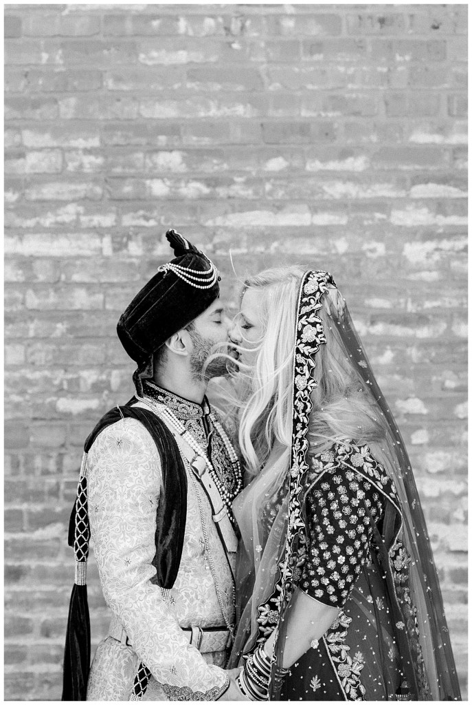 Black and white of bride and groom kissing in front of brick wall| Hindu wedding| Indian wedding Tulsa| Tulsa wedding photographer| Andi Bravo Photography
