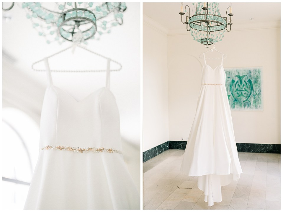 Wedding gown with gold trim belt hanging from gorgeous teal chandelier| The Mayo Tulsa| Tulsa wedding photographer| Destination wedding photographer| Andi Bravo Photography