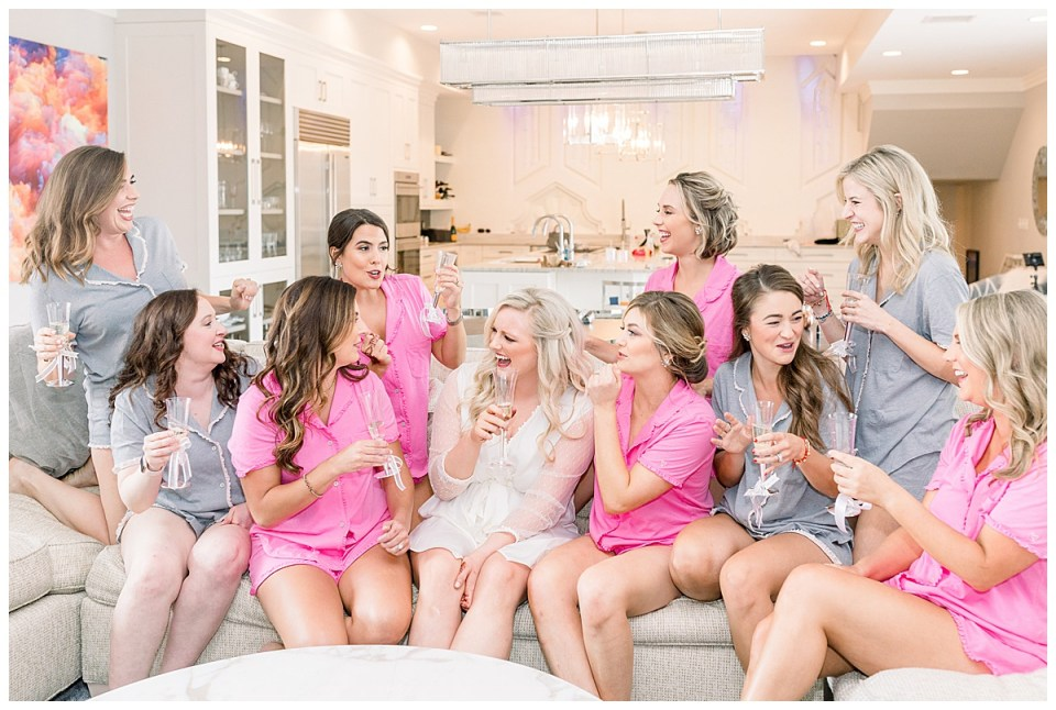 Bride and bridesmaids sitting on couch laughing and toasting in pink and grey pajamas| The Mayo Hotel Wedding| Tulsa wedding photographer| Destination wedding photographer| Andi Bravo Photography