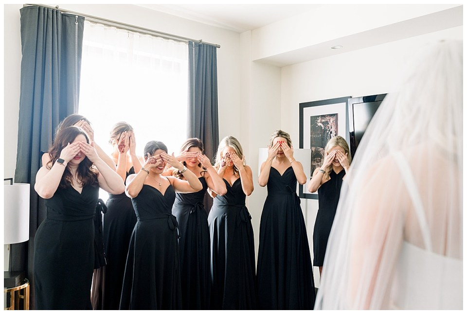 Bridesmaids stand in background covering their eyes while bride stands before them to reveal herself| The Mayo Hotel wedding| Tulsa wedding photographer| Andi Bravo Photography