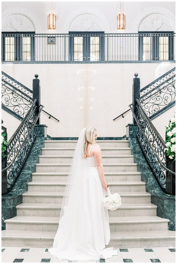 Bride stands below staircase in gown while looking over her shoulder holding white bouquet| The Mayo Hotel Wedding| Tulsa wedding photographer| Andi Bravo Photography