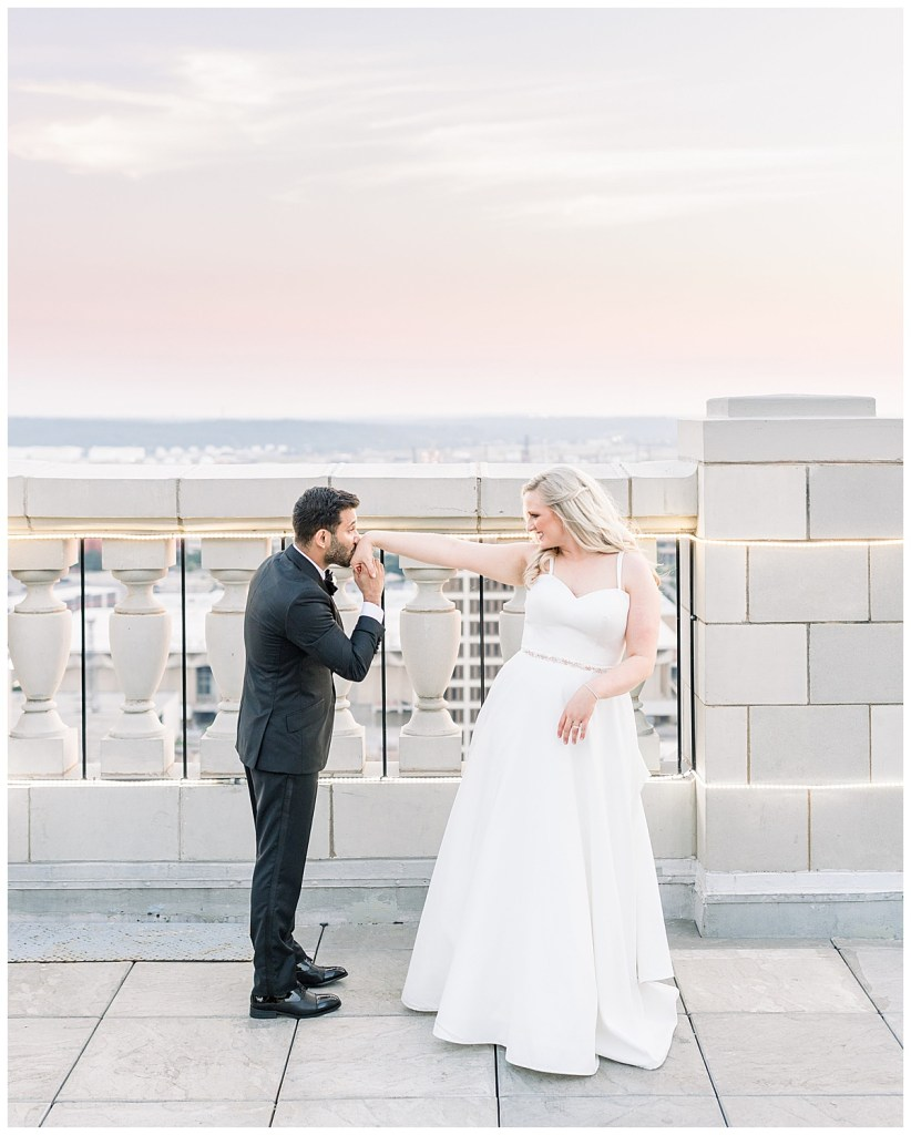 Groom kisses bride's outstretched hand on rooftop at sunset| The Mayo Hotel wedding| Tulsa wedding photographer| Andi Bravo Photography