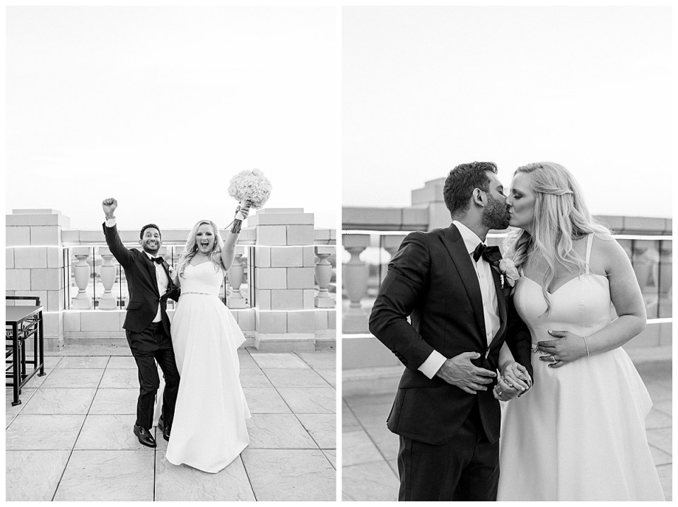 Black and white of bride and groom cheering and kissing on roof at The Mayo Hotel| Tulsa weddings| Tulsa wedding photographer| Destination wedding photographer| Andi Bravo Photography