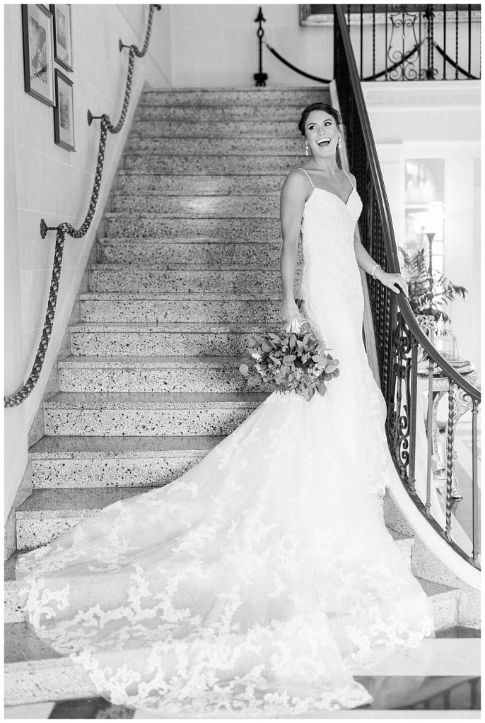 Black and white of bride standing and laughing on staircase with train flowing down stairs| Mansion at Woodward Park| Tulsa wedding venue| Tulsa wedding photographer| Andi Bravo Photography