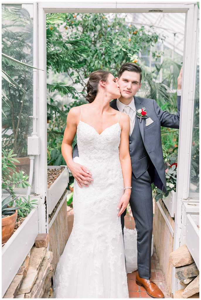 Bride smooches groom on cheek in greenhouse| Tulsa wedding venue| Andi Bravo Photography