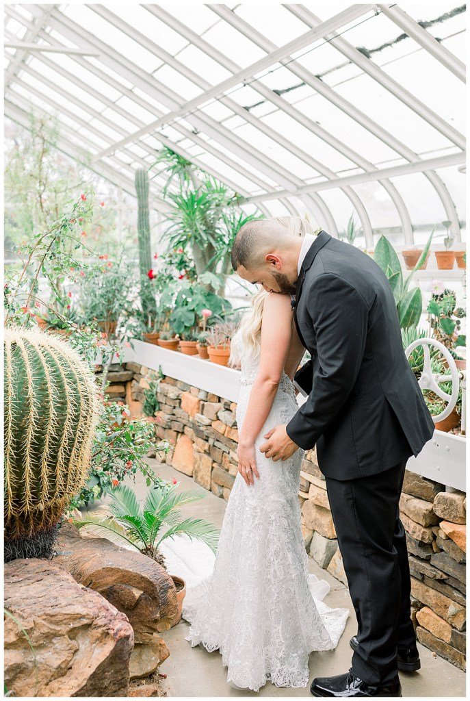 groom kisses bride on shoulder in greenhouse| greenhouse wedding first look| Andi Bravo Photography
