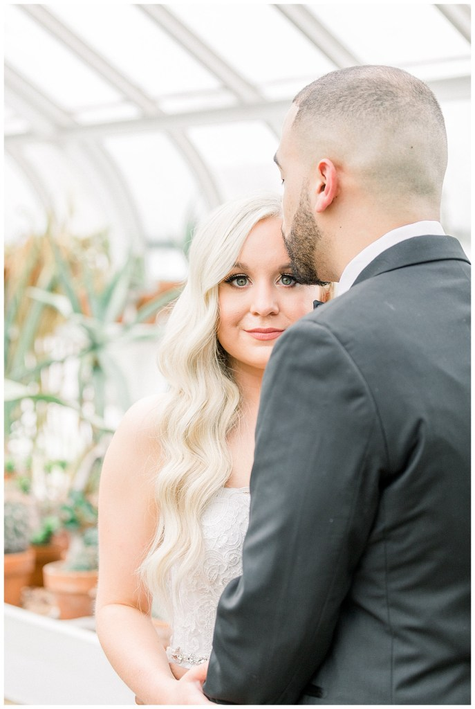 Bride looks into camera while groom kisses her on forehead| Forehead kisses| Wedding day first look| Tulsa wedding venue| Andi Bravo Photography