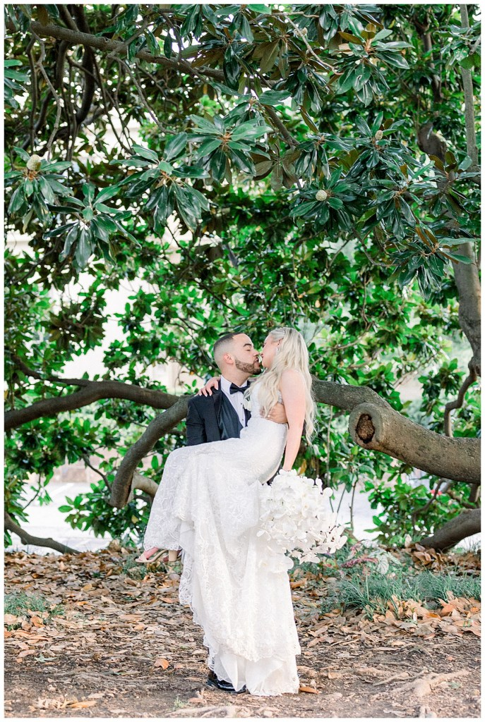 Groom sweeps bride off her feet and kisses her under huge tree| Tree wedding| Tulsa wedding venue| The Mansion at Woodward Park| Tulsa & destination wedding photographer| Andi Bravo Photography