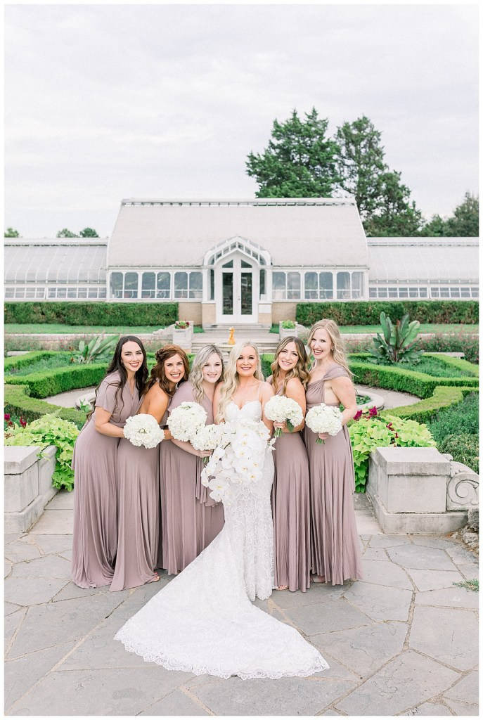 Bride and bridesmaids standing in front of Tulsa greenhouse| Tulsa weddings| Andi Bravo Photography