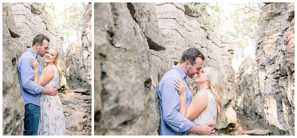 Couple snuggling and kissing on rocky pathway at Chandler Park Tulsa engagement