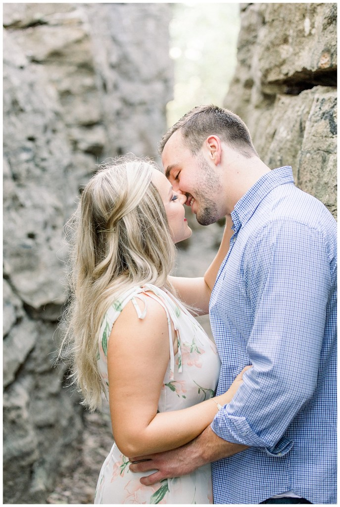 Couple kisses against rock wall in Tulsa Chandler Park engagement
