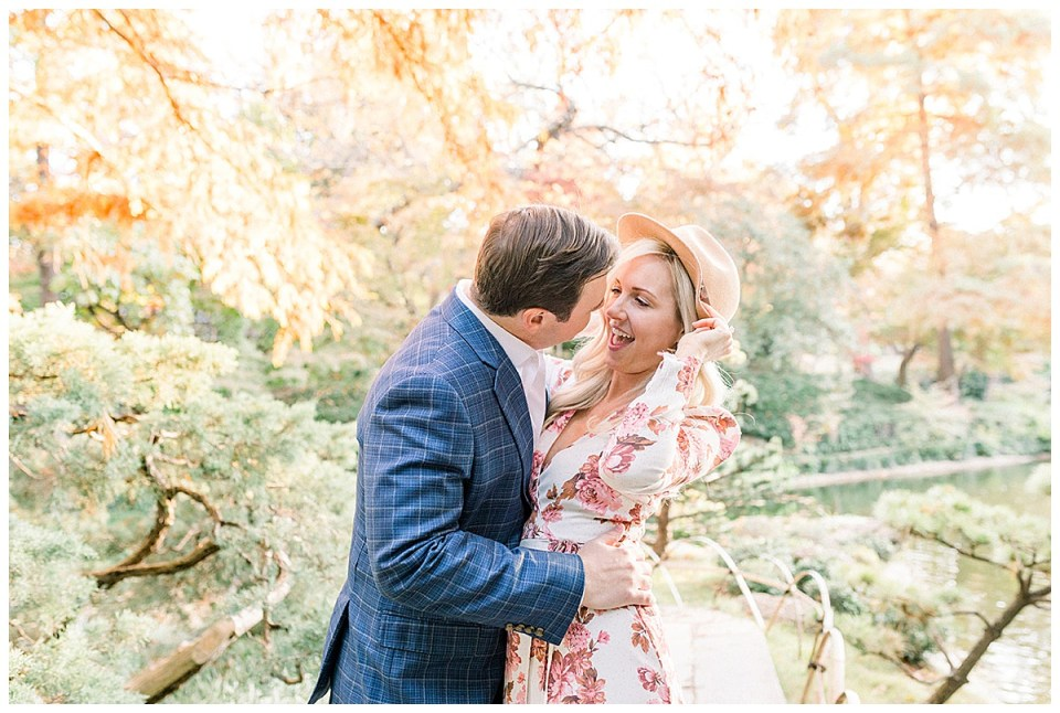 Girl giggles during embrace with guy at Fort Worth Botanical Gardens engagement