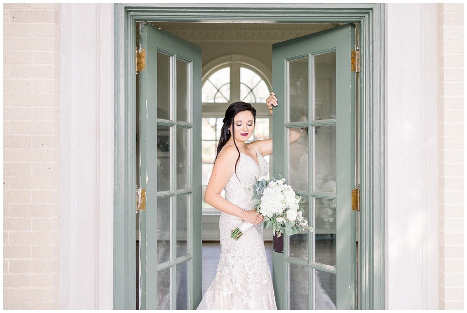 Bride standing between green doors