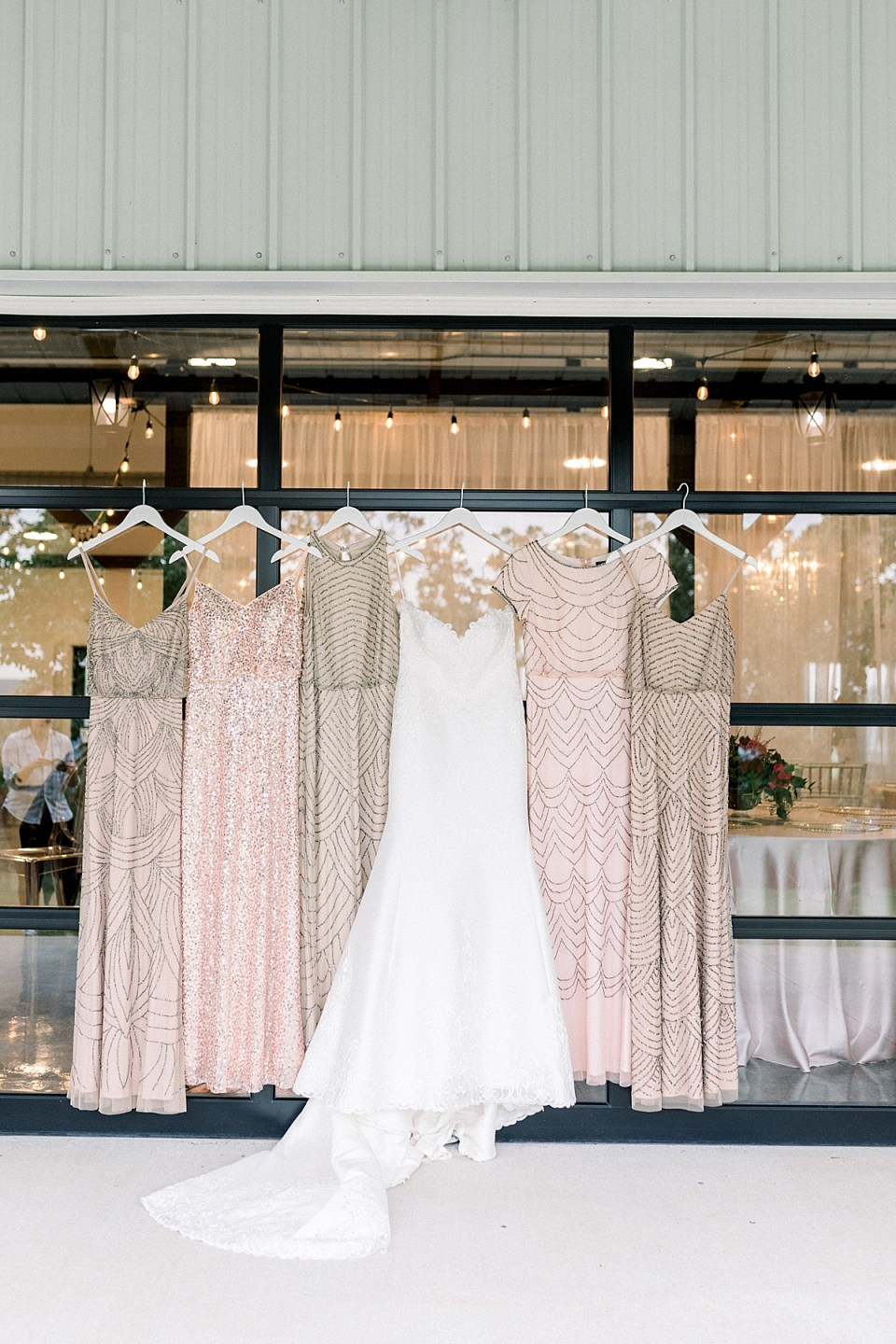 Art Deco bridesmaids dresses hanging with wedding gown at Dream Point Ranch Tulsa wedding venue