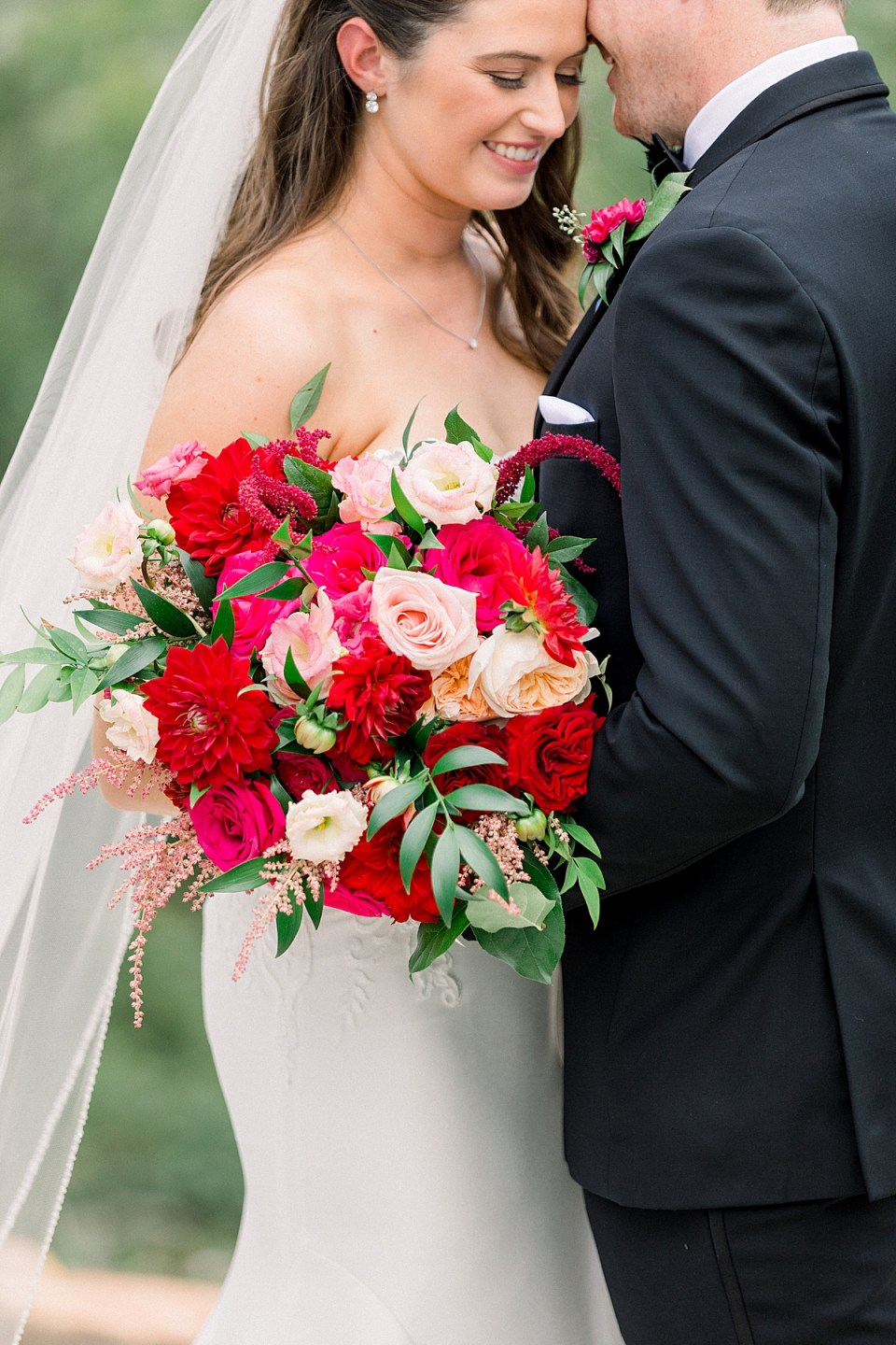 Bride and groom nuzzle with red and pink bridal bouquet
