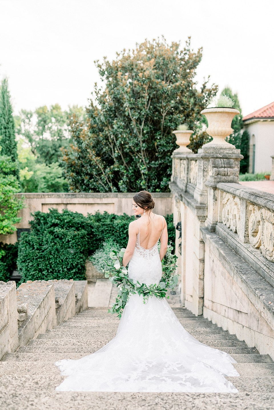 Bride standing on steps with train flowing behind her at Tulsa Philbrook bridal session