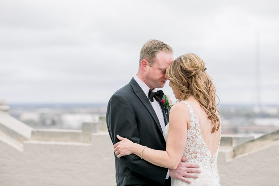 Bride and groom embrace on rooftop of Tulsa Club Hotel for wedding first look