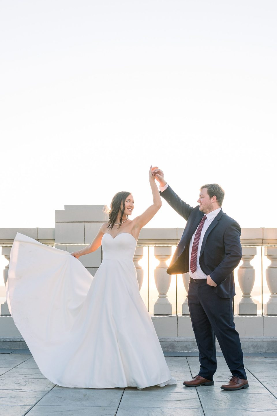 Bride and groom dance on rooftop of the Mayo Hotel at sunset