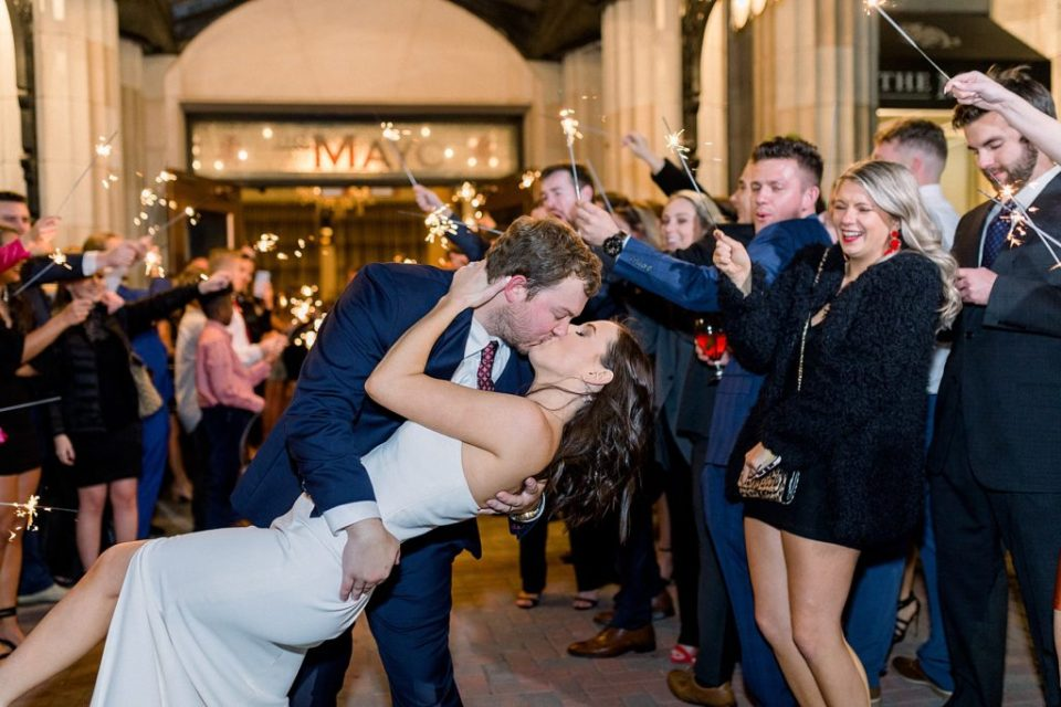 Groom dips bride for kiss during grand wedding exit at The Mayo Hotel