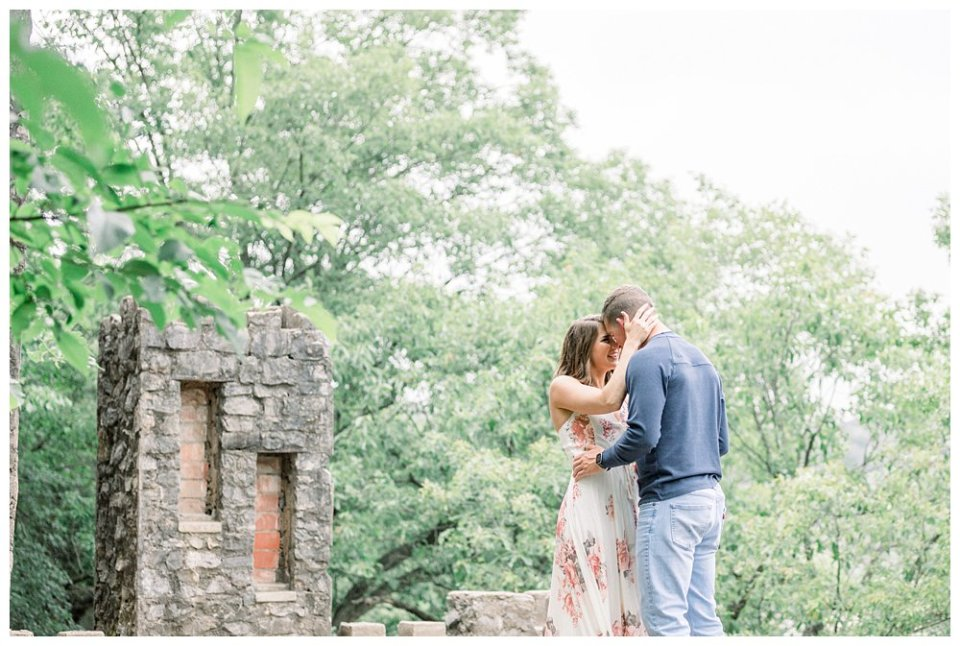 Couple nuzzling atop old castle ruins