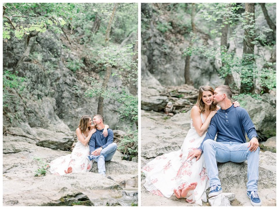 Couple sitting on rocks kissing surrounded by trees and stream