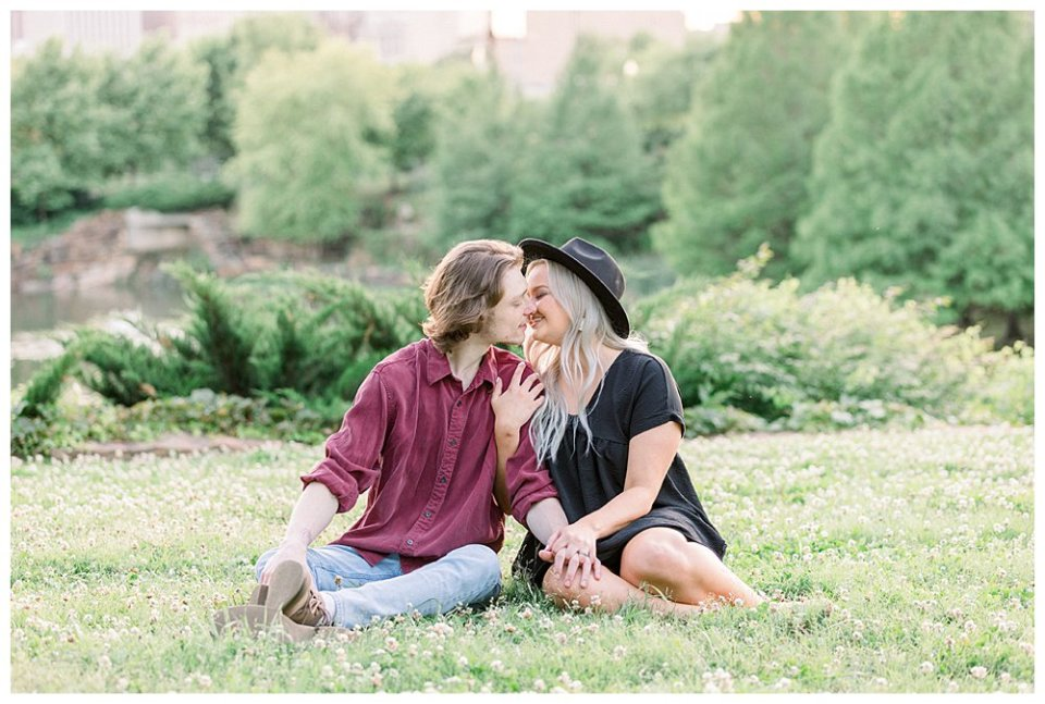 Couple sitting and kissing in grass  in Guthrie Green / Centennial Park Tulsa engagement
