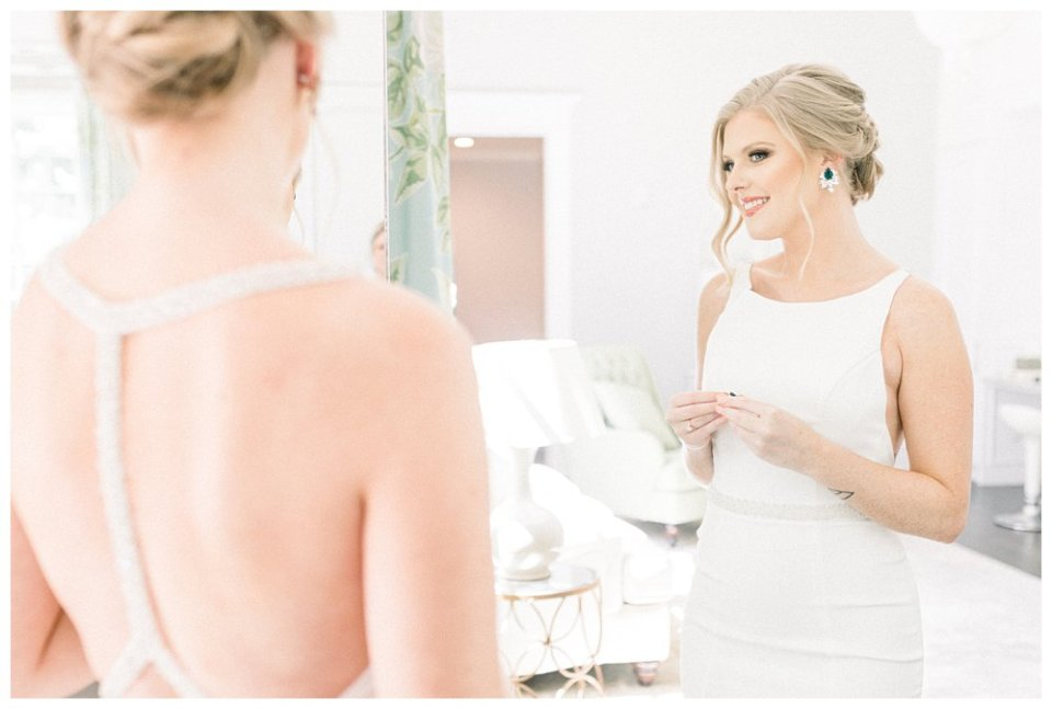 Bride putting earring on in mirror