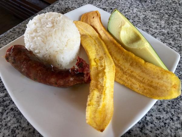 Longaniza, aguacate, arroz y plátano frito.