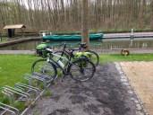 Zwei Fahrräder vor einem kleinen Hafenbecken mit Spreekähnen