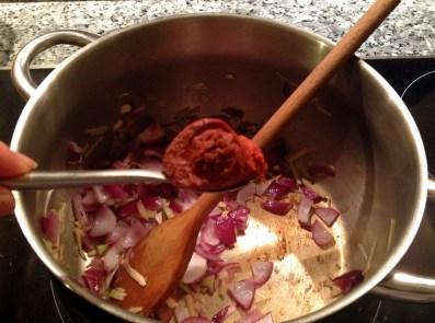 Adding Thai red curry paste