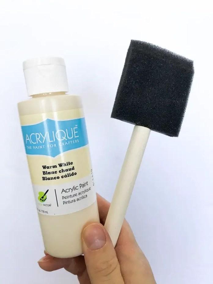 white acrylic paint and foam paint brush