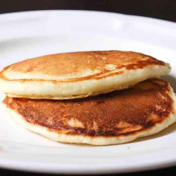 2 golden pancakes stacked together on a white plate with a black background