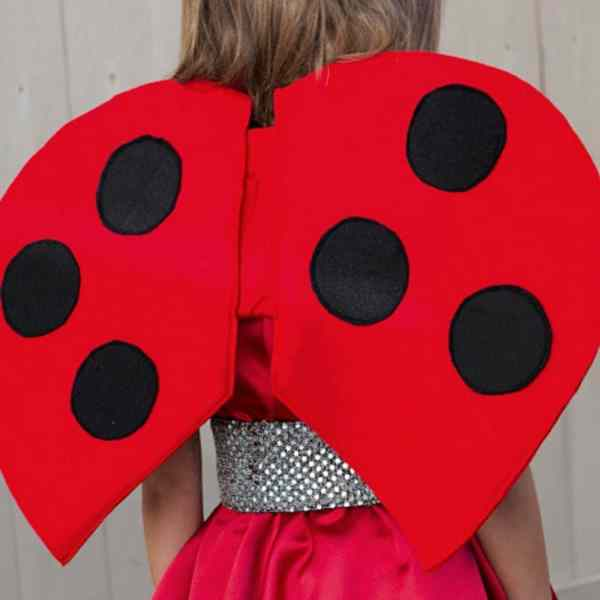 back view of kid wearing red ladybug wings with black polkadots. Wood fence in background.